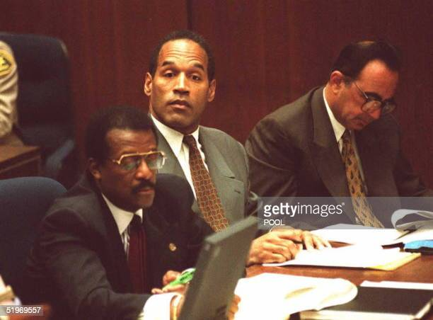 Simpson , flanked by his attorneys Johnnie Cochran and Robert Shapiro, looks up toward a deputy district attorney 12 January in a Los Angeles court....