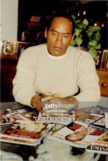 Simpson in his home a month after the acquittal looks at magazine stories about his case.
