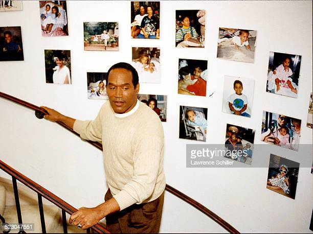 Simpson in his home a month after the acquittal with family photos in the background.