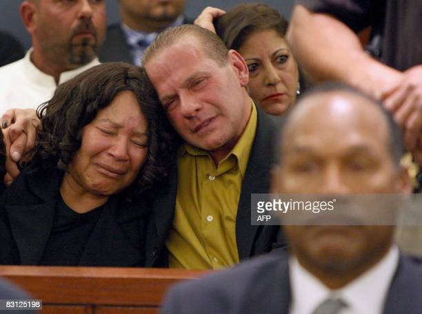 OJ Simpson looks on as his sister Carmelita Durio embraces friend Tom Scotto after a guilty verdict was read for her brother during his trial at the...