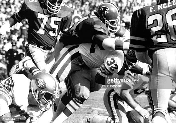 Simpson of the San Francisco 49ers is tackled by Wilson Faumuina of the Atlanta Falcons on November 5, 1978 at Atlanta-Fulton County Stadium in...