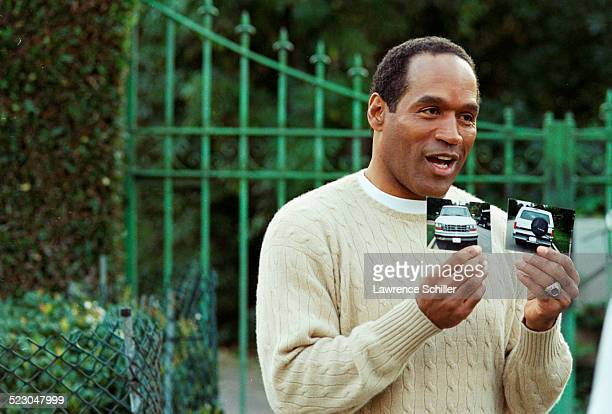 J Simpson outside his home months after his acquittal discussing the Bronco car he owned