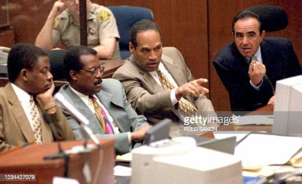 Simpson points to the video screen with his defense team of Carl Douglas, Johnnie Cochran Jr., Simpson and Robert Shapiro sit around him as Los...