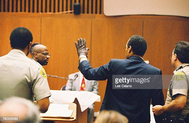 OJ Simpson shows the judge a leather glove allegedly used in the murders of Nicole Brown Simpson and Ronald Goldman during testimony in Simpson's...