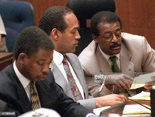J Simpson sits with defense lawyer Johnnie Cochran Jr and Carl Douglas looking at photographs 24 July during the OJ Simpson double murder trial...