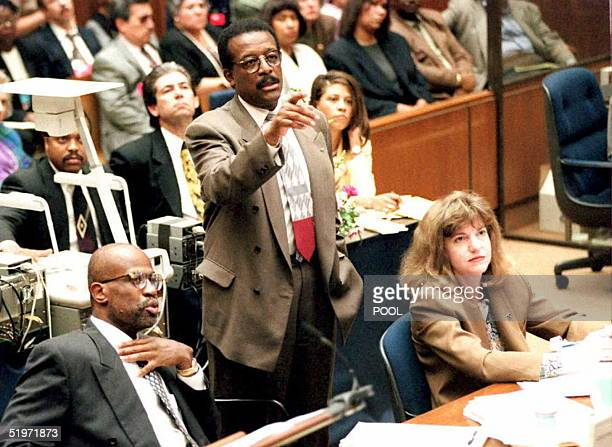 J Simpson's defense attorney Johnnie Cochran Jr flanked by prosecutors Christopher Darden and Sheri Lewis review evidence as Cochran redirects...