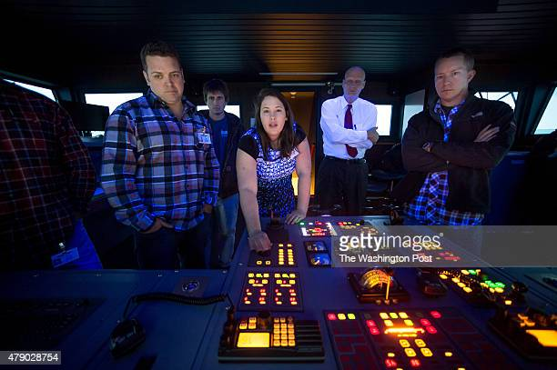Simulator Operator Catherine Horn center gives a quick briefing to Deck Officer students Jon Cornelius [cq] a chief mate and relief captain from...