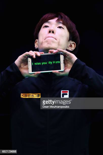 Sin da Woon of South Korea on the podium holds up a sign saying 'I miss you my hero' before he get his gold medal after the Men's 1500m race during...