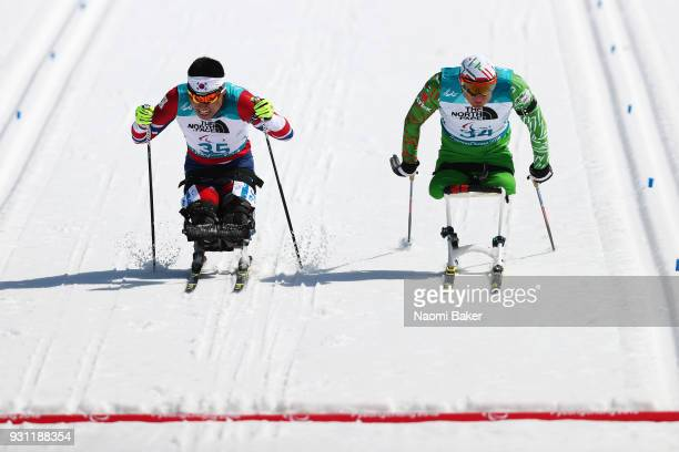 Sin Eui Hyun of South Korea beats Dzmitry Loban of Belarus battle it out to the finish line during the Men's Biathlon 125km Sitting on day four of...