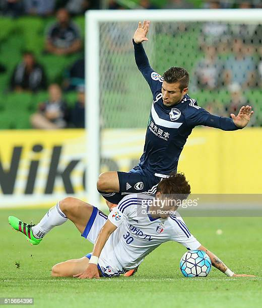 Sin Se Gye of Suwon and Kosta Barbarouses of the Victory compete for the ball during the AFC Champions League match between the Melbourne Victory and...