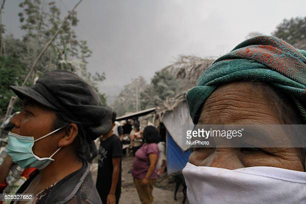Sinabung volcano refugees scrambled to protect themselves from the thick volcanic ash following the recent eruption of Mount Sinabung in Teacher...