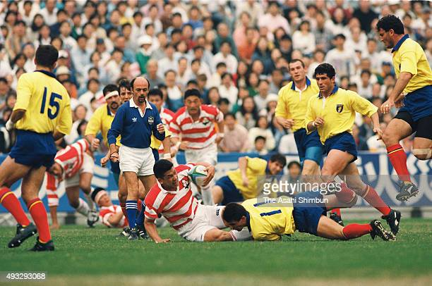Sinali Latu of Japan is tackled by Romania defense during the international friendly match between Japan and Romania at the Prince Chichibu Stadium...