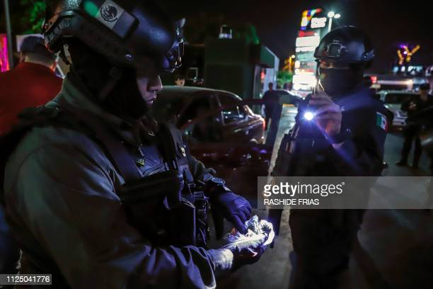Sinaloa state police agents check a plastic bag with a suspicious substance found during a security operation in the city of Culiacan, Sinaloa state,...