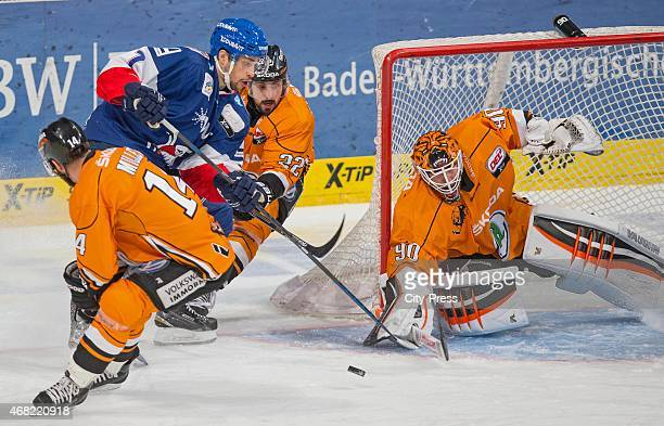 Sinan Akdag of the Adler Mannheim and Felix Brueckmann of the Grizzly Adams Wolfsburg fight for the puck during the game between Adler Mannheim and...