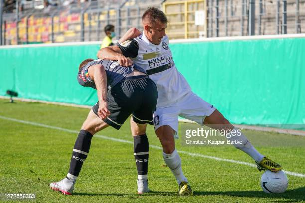 Sinan Tekerci of SV Elversberg challenges Sebastian Ohlsson of FC St. Pauli during the DFB Cup first round match between SV Elversberg and FC St....