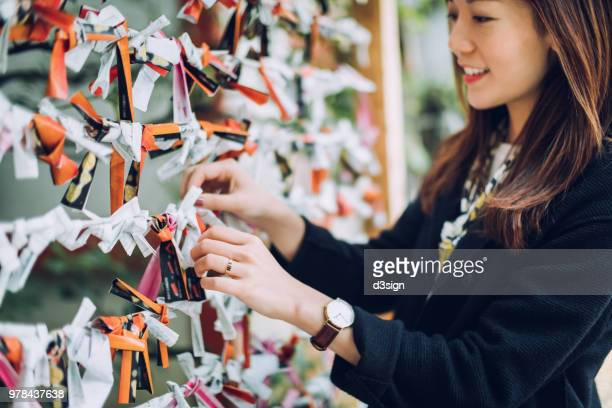 sincere young woman making a wish and tying a prayer blocks - shrine stock pictures, royalty-free photos & images