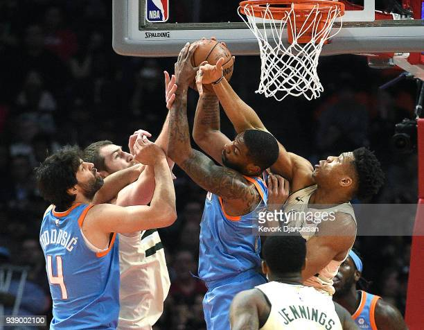 Sindarius Thornwell of the Los Angeles Clippers pulls down a rebound against Tyler Zeller and Giannis Antetokounmpo of the Milwaukee Bucks with...