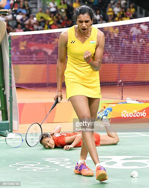 PV Sindhu of India reacts as Japan's Nozomi Okuhara watches while lying on the court during a women's badminton singles semifinal match at the Rio de...