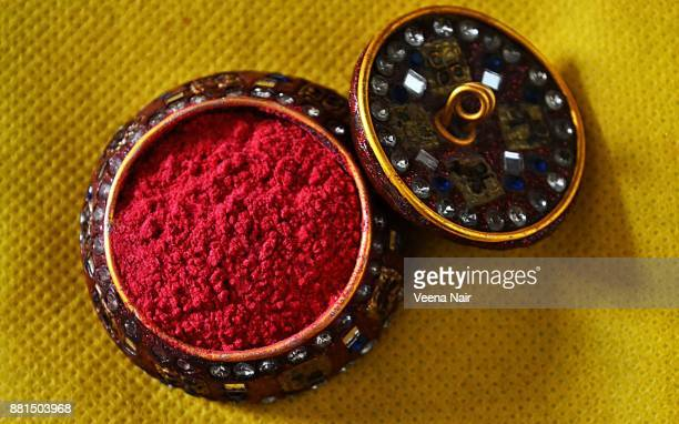Sindoor/Vermilion/Kumkum in a Lac ornate container against yellow background