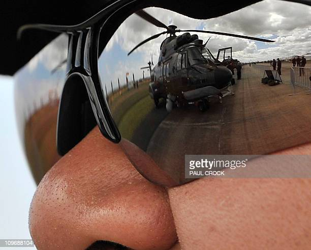 A Singapore Air Force SuperPuma Helicopter is reflected in the glasses of its pilot on the opening day of the Australian International Airshow and...