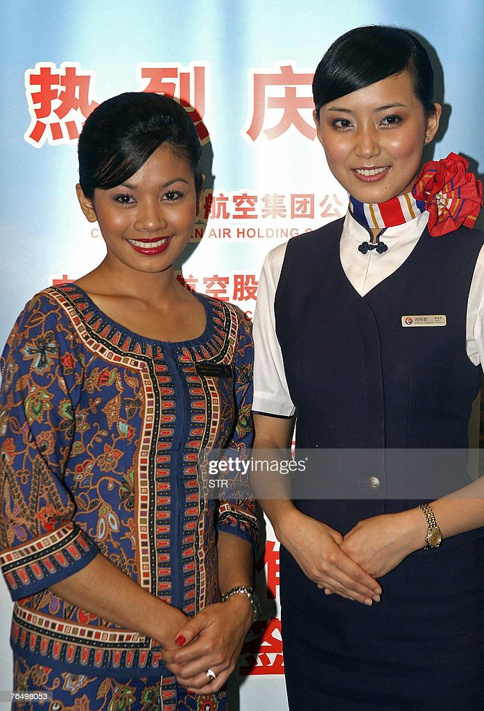 a singapore airlines and a china eastern airlines cabin crew pose