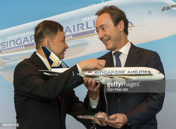 Singapore Airlines chief executive officer Goh Choon Phong presents a SIA plane model to Airbus chief operating officer Fabrice Bregier during the...