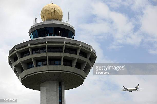 A Singapore Airlines Ltd aircraft flies past the air traffic control tower after taking off at Changi Airport in Singapore on Wednesday Oct 31 2012...
