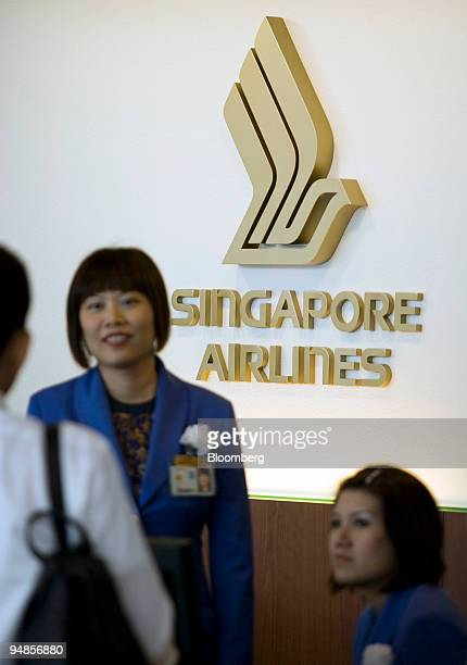 Singapore Airlines Ltd employees speak with a customer at Changi airport in Singapore on Thursday Nov 6 2008 Singapore Airlines Ltd Asia's most...