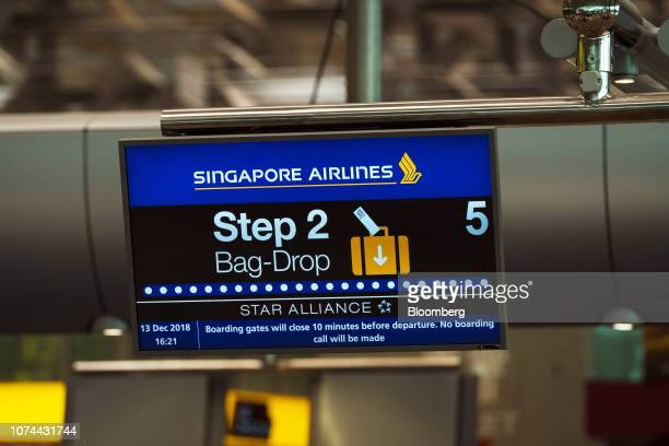 A Singapore Airlines Ltd logo is displayed on a monitor atop automated luggage dropoff machines in the departure hall at Terminal 3 of Changi Airport...