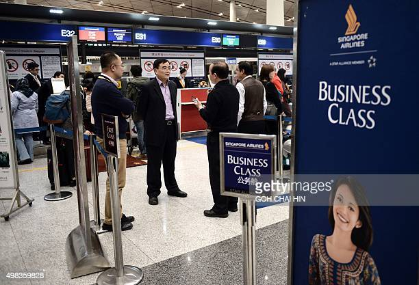 Singapore airlines' passengers wait for their flights at the Beijing Capital International airport after heavy snowstorm cancelled and delayed...