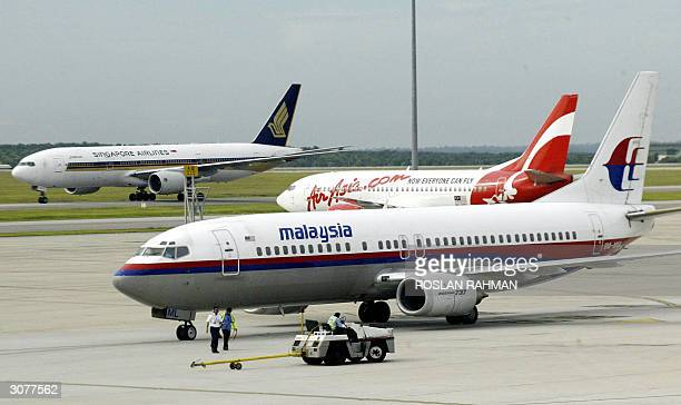 Singapore Airlines plane taxis down the runway passing by a AirAsia and a Malaysian Airline System planes at the terminal of Kuala Lumpur...