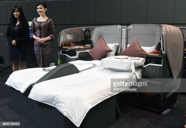Singapore Airlines staff members stand next to a display of its business class seat during the launch of new cabin products and inflight experiences...
