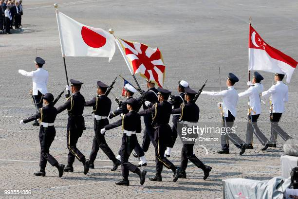 Singapore and Japanese troops march with flags during the traditional Bastille Day military parade on the ChampsElysees Avenue on July 14 2018 in...