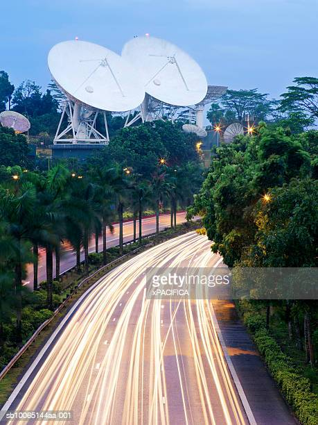 Singapore, blurred traffic on highway with satellite dishes in background, elevated view