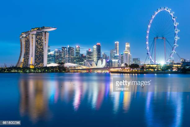 singapore city, singapore - 29th january 2017: singapore city skyline with marina bay sands hotel (left) and the singapore flyer ferris wheel - singapore flyer stock photos and pictures