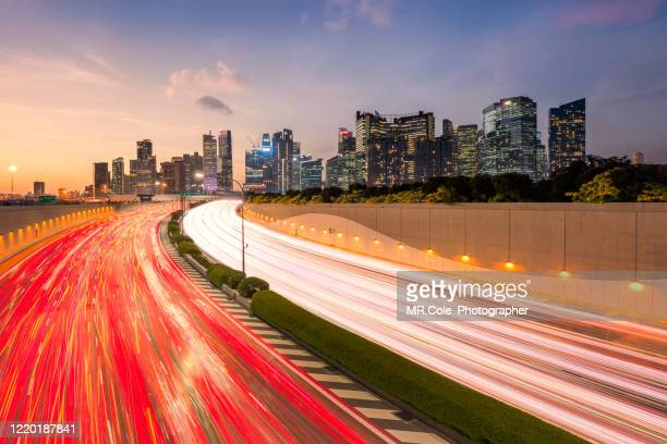 singapore city with street light of traffic road on motorway or highway,buildings in business district ,financial economy, construction industry,modern company organization concept - singapore stock pictures, royalty-free photos & images