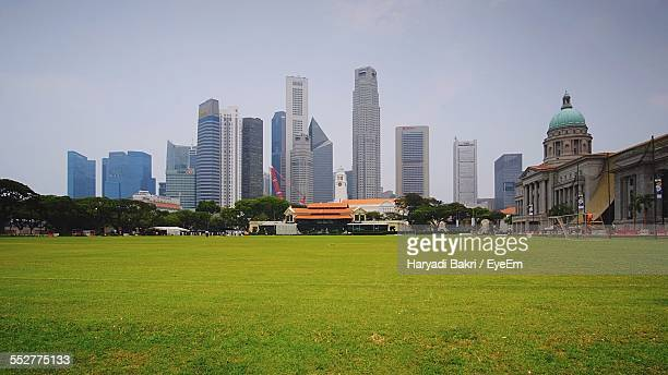 singapore cricket assn by modern buildings against sky - cricket pitch stock pictures, royalty-free photos & images