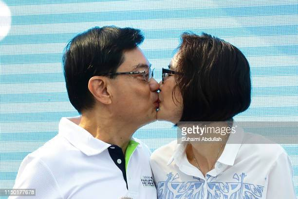 Singapore Deputy Prime Minister and Minister of Finance, Heng Swee Keat kisses his wife, Chang Hwee Nee during the launch of Celebrating Fathers' -...
