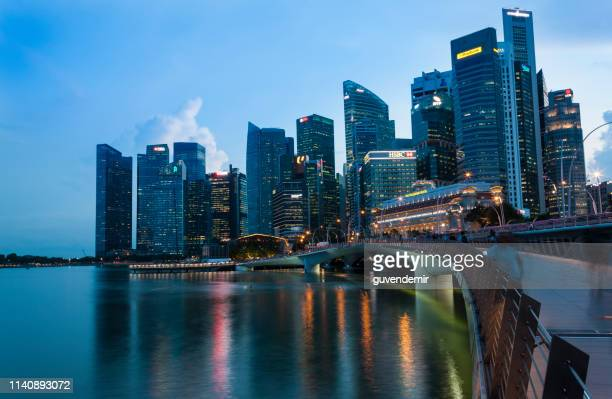 singapore financial district skyline at marina bay on twilight time - association of southeast asian nations stock pictures, royalty-free photos & images