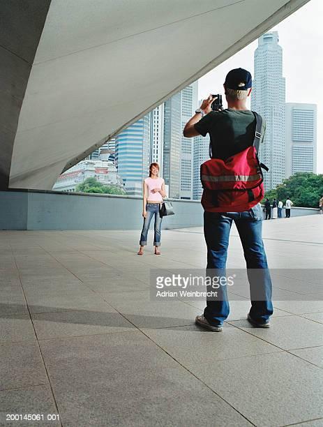 Singapore, man taking photograph of woman under bridge