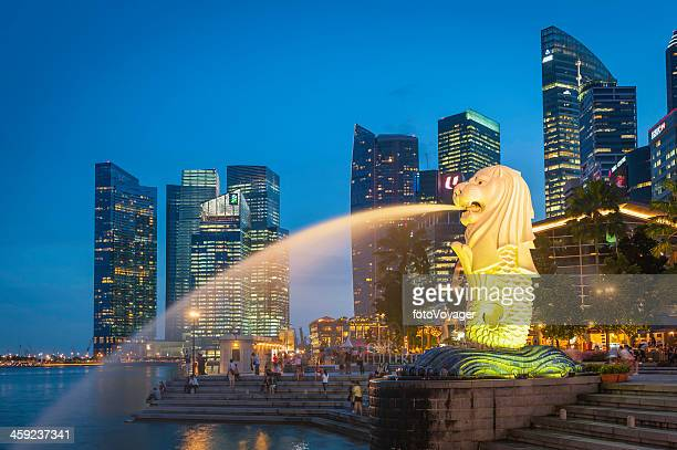 singapore merlion fountain and marina bay skyscrapers illuminated at dusk - merlion stock pictures, royalty-free photos & images