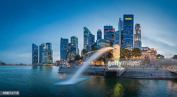 singapore merlion fountain cbd skyscrapers overlooking marina bay at dusk - merlion stock pictures, royalty-free photos & images