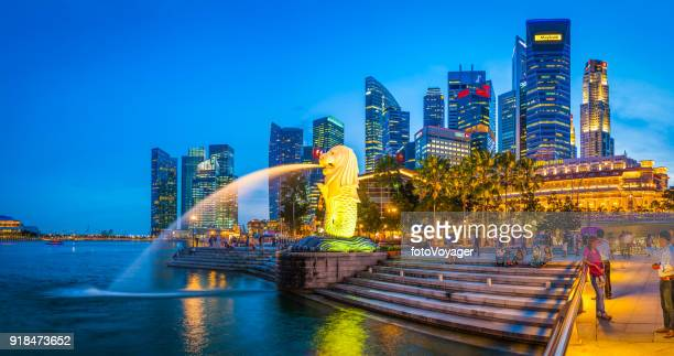singapore merlion fountain people enjoying evening below marina bay skyscrapers - merlion park stock photos and pictures