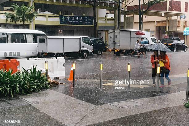 singapore la stagione dei monsoni pioggia, un ombrello condivisione - pioggia forte foto e immagini stock