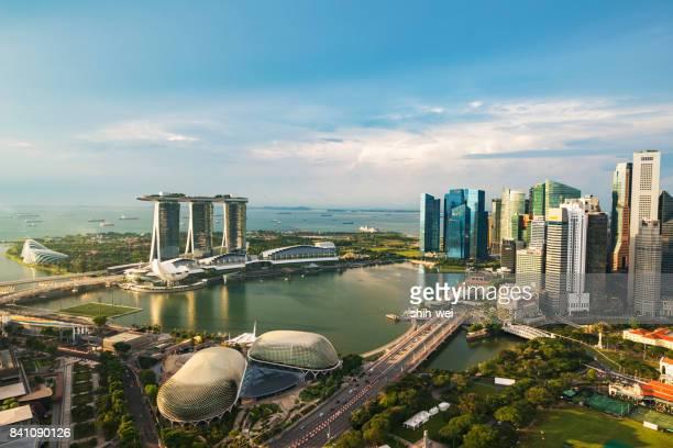 singapur: motorboot marina bay kreuzen. cloud-garten und supertrees hain fviewed von marina east park mit blumen im vordergrund - marina bay singapur stock-fotos und bilder