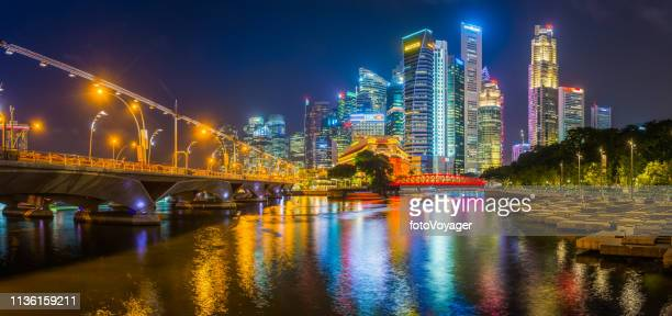 singapore neon night skyscrapers glittering over singapore river bridges panorama - singapore city stock pictures, royalty-free photos & images
