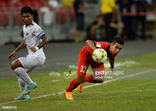 Singapore player Muhammad Zulfahmi dribble pass Mynmar player Khin Maung Lwin during their AFF Suzuki Cup 2014 football match at the National Stadium...