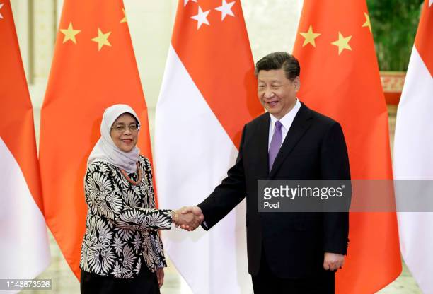 Singapore President Halimah Yacob and Chinese President Xi Jinping shake hands at the Great Hall of the People on May 14 2019 in Beijing China