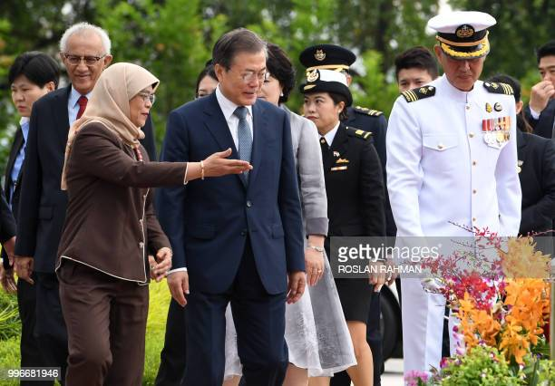 Singapore President Halimah Yacob shows the way to South Korean President Moon Jaein to a welcoming ceremony ceremony at Istana presidential in...