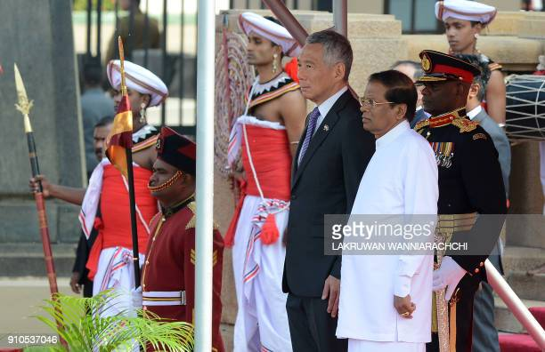 Singapore Prime Minister Lee Hsien Loong and Sri Lankan President Maithripala Sirisena stand at attention during a welcoming ceremony at the...